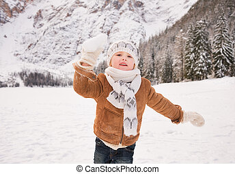 Child throwing snowball outdoors among snow-capped mountains...