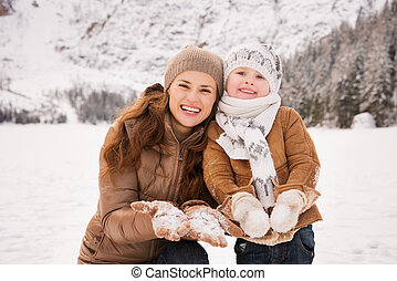 Mother and child showing snowy gloves in winter outdoors -...