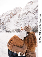 Seen from behind mother pointing child on snow-capped...