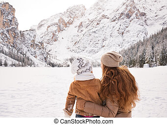 Seen from behind mother and child looking on snow-capped...