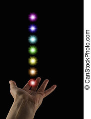 The Seven Chakras - Female healer's hand palm up with a...