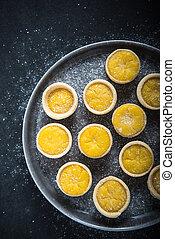 Mini lemon custard tarts on plate, from above