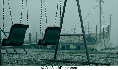 Two swings in the fog autumn atmosphere. Swings in the...