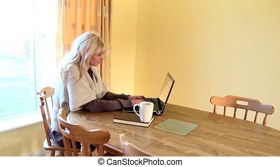 Enthusiastic woman using a laptop and drinking coffee at...