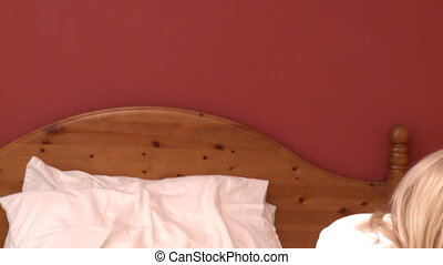 Delightful woman on phone lying down on bed at home