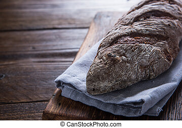Whole loaf of artisan bread on wooden rustic cutting board
