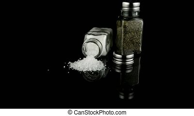 Salt and oregano shakers - Salt and oregano shakers on black...