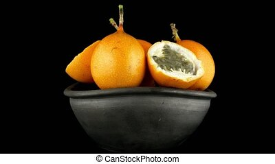 Passion fruit maracuja granadilla on ceramic black bowl,...