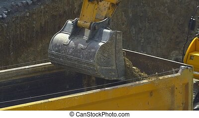 Excavator loading soil dump truck - Slow motion close up...