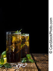 Cold Longdrink Cuba Libre with brown rum and fresh lime on...
