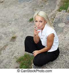 Close portrait of sexy fashion blonde who smokes a cigarette...