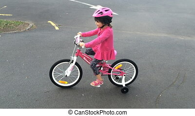 Little age 5 girl ride new bicycle in the park