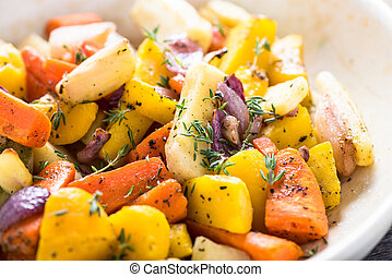 Roasted and baked root vegetables in rustic tray with fresh...
