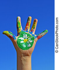 Painted kid hand with flower daisy on a blue sky background