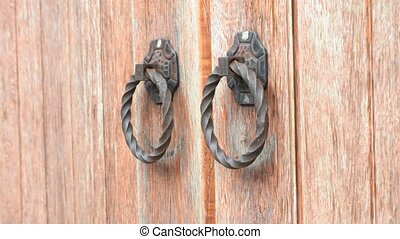 Hand knocking on old-fashioned ancient wooden gate or door -...