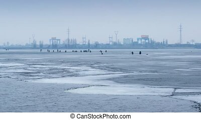 Time lapse with zoom effect of winter fishermen angling on...
