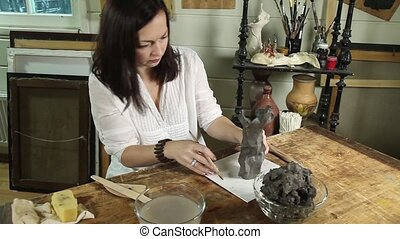 Sculptor working with clay in a studio