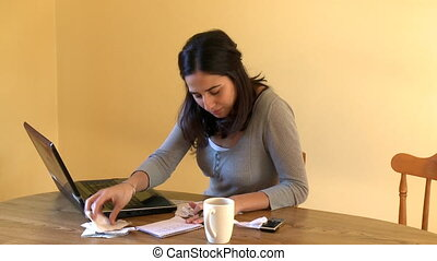 Unhappy woman doing her accounts at home