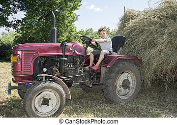 Summer bright sunny day boy is carrying hay on the tractor.