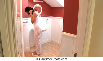Brunette woman weighing herself in the bathroom