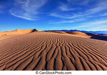 Stovepipe Wells Village - Thin waves on sand. Bright solar...