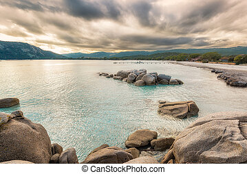 Boulders in a turquoise sea at Santa Giulia beach in Corsica...