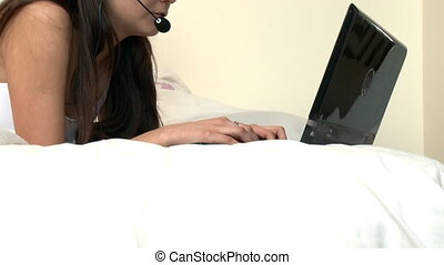 Brunette woman with headset on using a laptop lying down on...