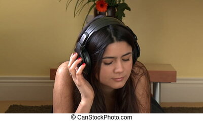 Brunette woman listening music lying down on bed at home