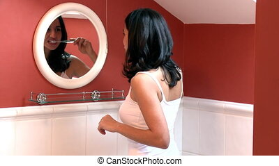 Brunette woman brushing her teeth in the bathroom