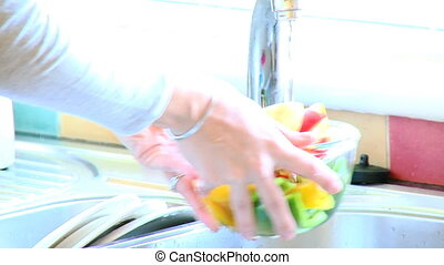 Cute woman rinsing vegetables - Close-up of a woman rinsing...