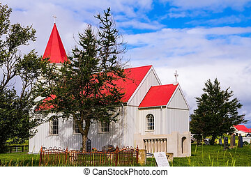 Fancy rural church with red roof on green lawn. Travel to...