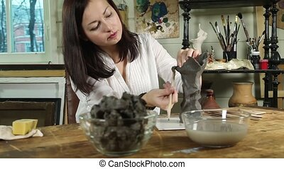 Woman sculpts from raw clay - Artist woman sculpts from raw...