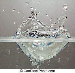Ice cube falling into water bowl with the spash frozen in...