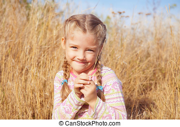 Joyful girl on nature with a blade of grass in hands
