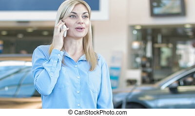 Pleasing female customer talking happily on the phone -...