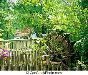 vintage water mill wheel running near a wooden bridge -...