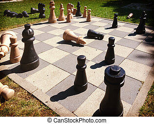 chess game board outdoors with king size wooden pieces on a...