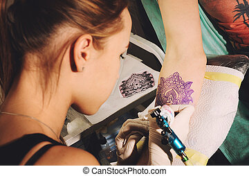 Girl tattoo artist makes tattoo on a hand against blue...