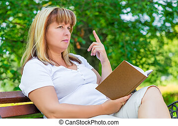 pensive woman with a book in the park