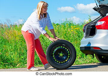 50-year-old woman have prepared to replace the spare wheel