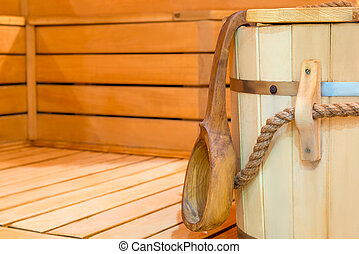 Wooden bucket and ladle in sauna close up