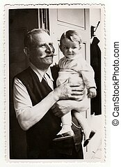 A small girl with her grandfather. Vintage photo was taken...