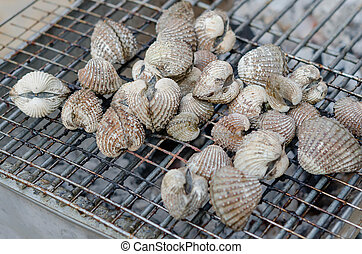 Cockles on flaming grill - close up seafood bbq , cockles on...