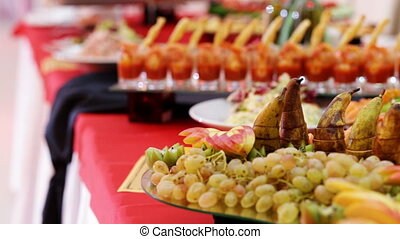 Smorgasbord table covered with colored cocktails and snacks...