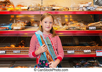 Little girl choosing bread in a food store