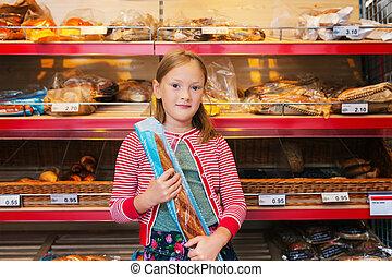 Little girl choosing bread in a food store