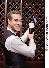 Handsome male waiter is analyzing quality of drink -...