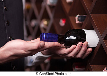 Experienced male worker is choosing drink in cellar - Close...
