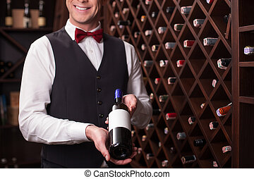 Cheerful winehouse worker is presenting elegant beverage - I...