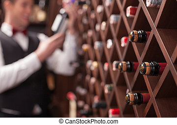 Professional waiter is making decisions about drink -...